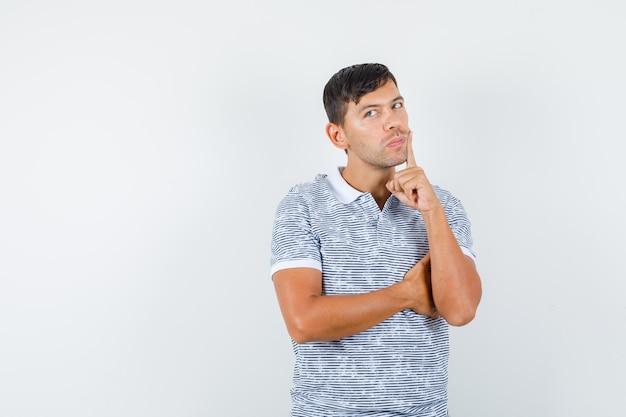 口の近くで指を保持し、物思いにふけるtシャツの若い男性