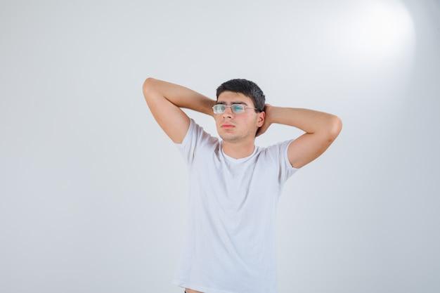 頭の後ろで手を握り、リラックスして見えるtシャツの若い男性、正面図。