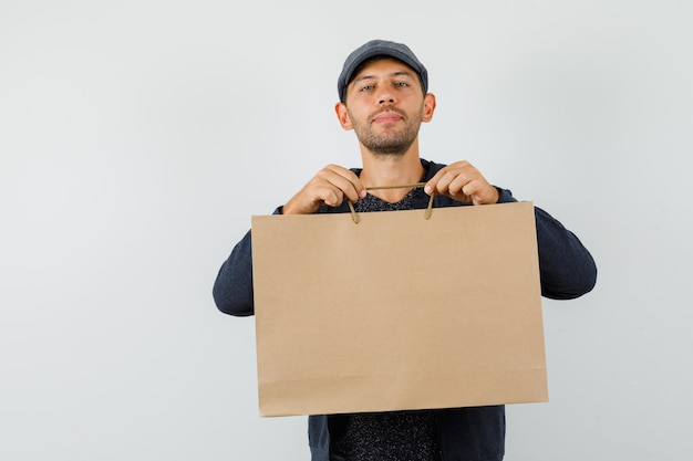 Молодой мужчина в футболке, куртке, кепке держит бумажный пакет и улыбается, вид спереди.