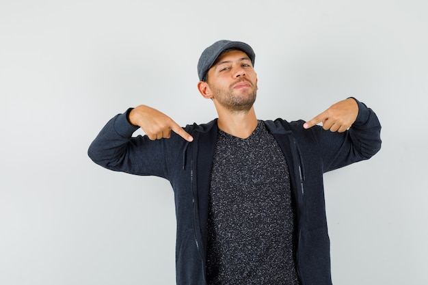 Молодой мужчина в футболке, куртке, кепке, указывая на себя и уверенно, вид спереди.