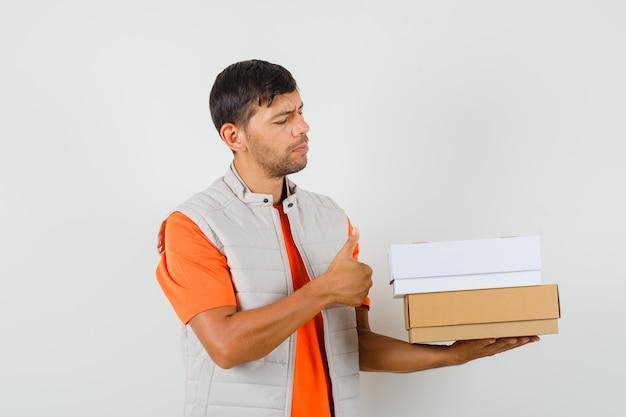 Молодой мужчина в футболке, пиджаке держит картонные коробки, показывает палец вверх, вид спереди.