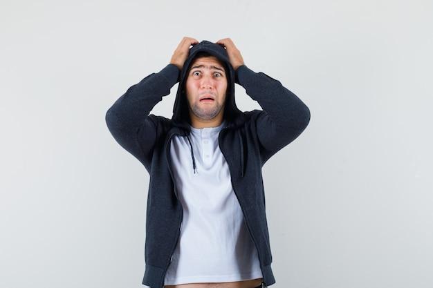 T- 셔츠, 재킷 머리에 손을 잡고 곰 곰, 전면보기에 젊은 남성.