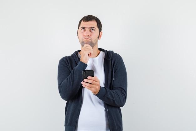 Молодой мужчина в футболке, куртке с мобильным телефоном и задумчивый вид спереди.