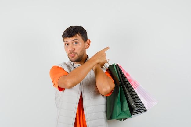 Tシャツを着た若い男性、買い物袋を保持しているジャケット、離れて、正面図。