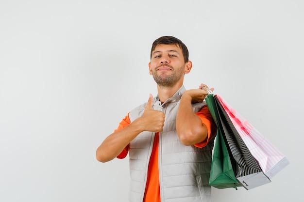 Tシャツを着た若い男性、買い物袋を持ったジャケット、親指を立てて陽気に見える、正面図。