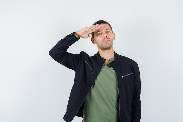 Молодой мужчина в футболке, куртке делает салютный жест и выглядит уверенно, вид спереди.