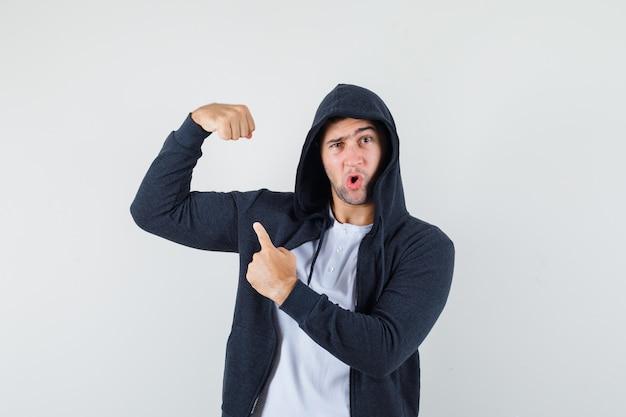 T- 셔츠, 팔의 근육을 가리키고 자신감, 전면보기를 찾고 재킷에 젊은 남성.