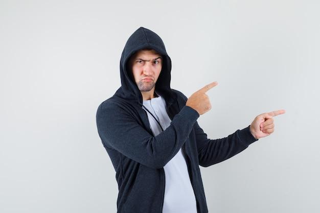 T- 셔츠, 재킷 오른쪽을 가리키고 의심스러운, 전면보기에 젊은 남성.