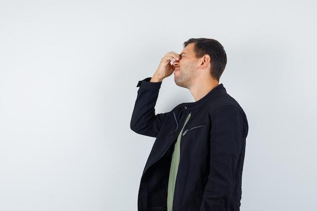 Молодой мужчина в футболке, пиджаке потирает глаза и нос и выглядит забывчивым.