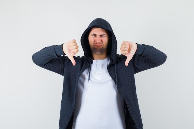 Tシャツを着た若い男性、二重の親指を下に向けて不機嫌そうに見えるジャケット、正面図。