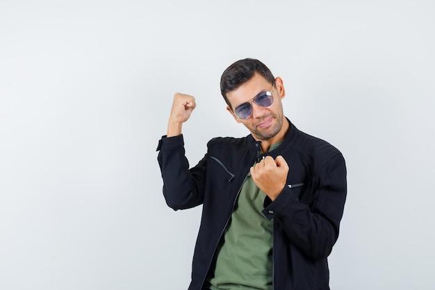 Молодой мужчина в футболке, куртке показывает жест победителя и выглядит счастливым, вид спереди.