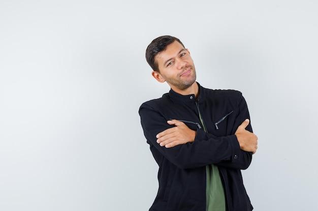 Tシャツを着た若い男性、腕を組んで立っているジャケット、陽気に見える、正面図。