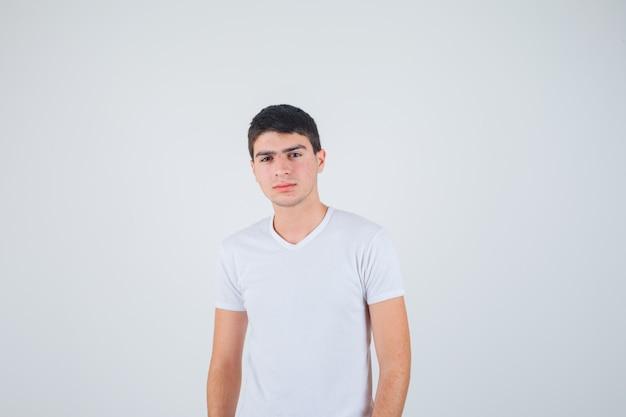 カメラを見て自信を持って、正面図を見てtシャツの若い男性。