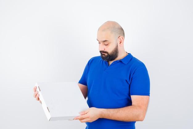 티셔츠를 입은 젊은 남성은 닫힌 피자 상자를 보고 자신감 있고 앞모습을 보고 있습니다.