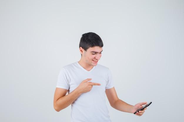 전화를 가리키고 메리, 전면보기를 찾고 t- 셔츠에 젊은 남성.