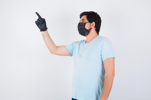 Молодой мужчина в футболке, указывая на верхний левый угол и глядя сосредоточенно, вид спереди.