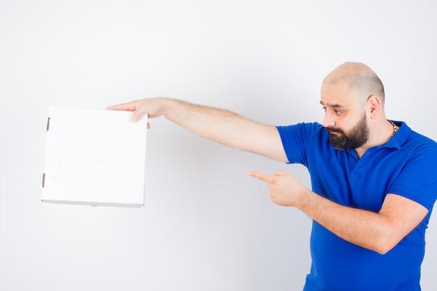 左側を指して、焦点を合わせて、正面図を探しているtシャツの若い男性。