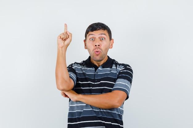 티셔츠를 입은 젊은 남성이 위를 가리키고 겁에 질린 듯 정면을 바라보고 있습니다.