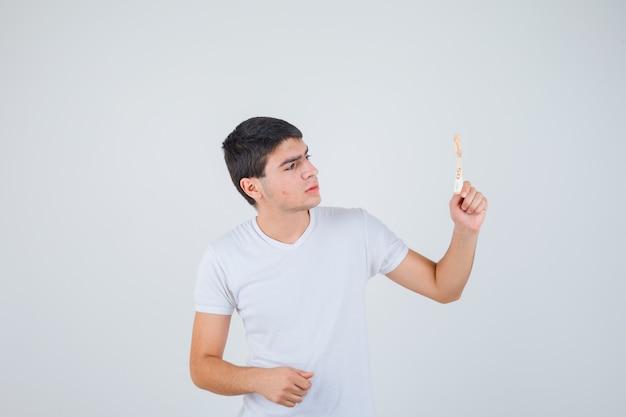 Молодой мужчина в футболке поднимает руку с банкнотой евро и выглядит уверенно, вид спереди.