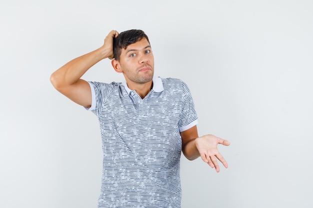 頭を掻いて無力に見えるtシャツの若い男性