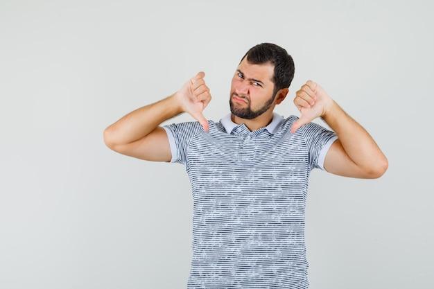 Молодой мужчина в футболке показывает двойные пальцы вниз и выглядит недовольным, вид спереди.