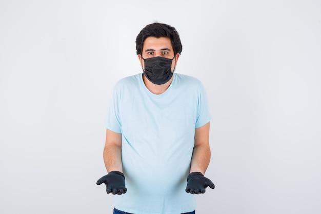 Молодой мужчина в футболке показывает беспомощный жест и выглядит смущенным, вид спереди.