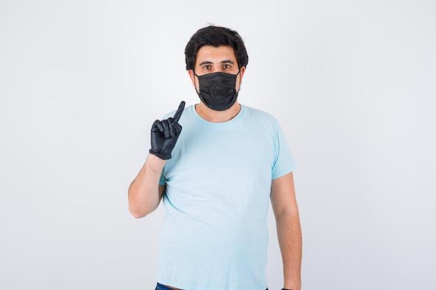 Молодой мужчина в футболке показывает номер один и выглядит серьезным, вид спереди.