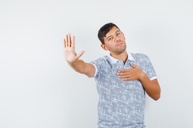 丁寧に拒否ジェスチャーを示すtシャツの若い男性