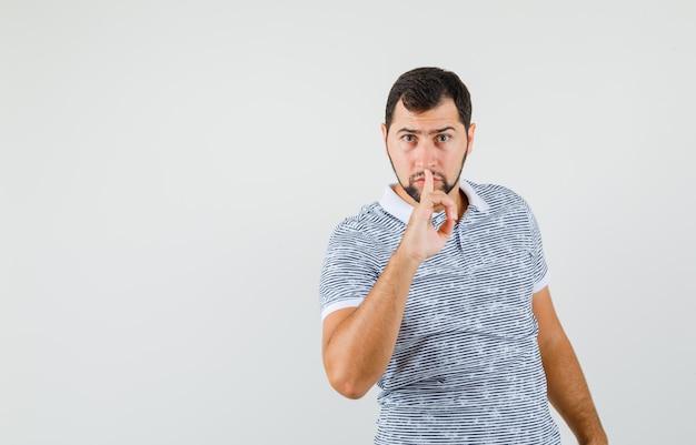沈黙のジェスチャーを示し、真剣に見えるtシャツの若い男性、正面図。