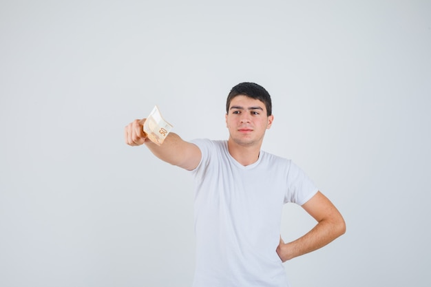 Молодой мужчина в футболке протягивает руку с банкнотой евро и выглядит уверенно, вид спереди.