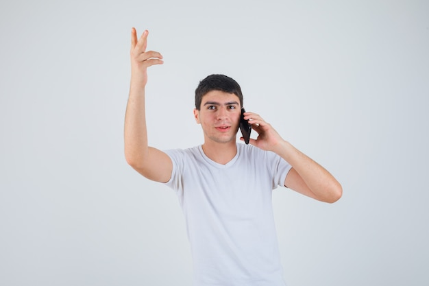 腕を上げて、焦点を合わせて見ながら携帯電話で話しているtシャツの若い男性、正面図。