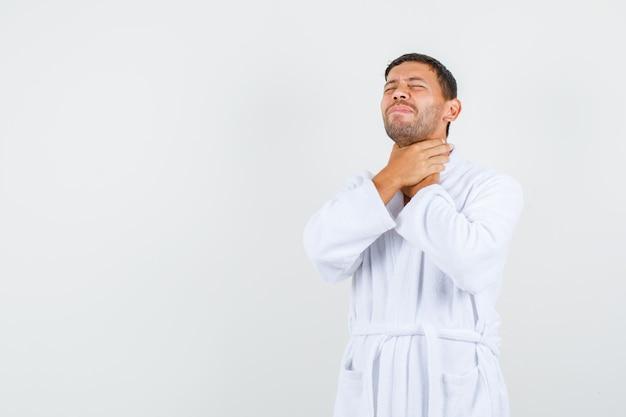 彼の喉に手をつないで、痛みを伴う、正面図を見て白いバスローブを着た若い男性。