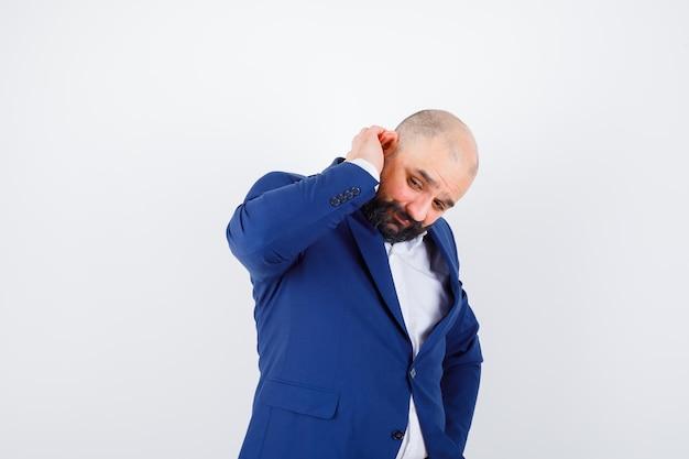 Молодой мужчина в белой рубашке, куртке, держащей руку за ухом и задумчивой, вид спереди.