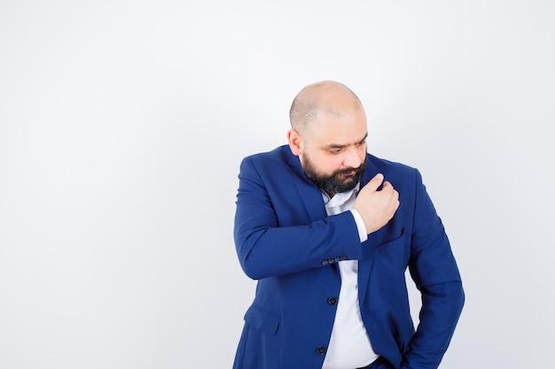 Молодой мужчина в белой рубашке, пиджаке демонстрирует превосходство, вытирая плечо, и выглядит скрупулезно, вид спереди.
