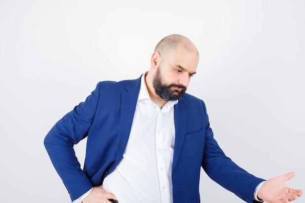 Молодой мужчина в белой рубашке, куртке, показывающей что-то внизу и задумчивой, вид спереди.
