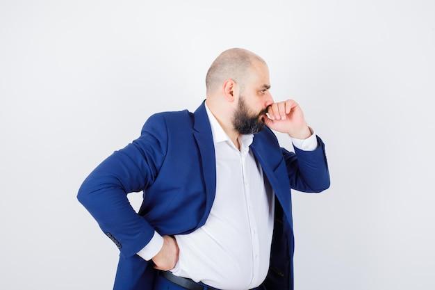 Молодой мужчина в белой рубашке, куртке, стоя в позе мышления и нерешительно глядя, вид спереди.
