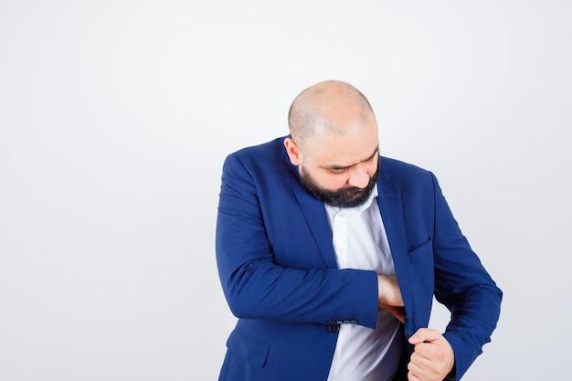 Молодой мужчина в белой рубашке, пиджаке вынимает что-то из кармана и выглядит элегантно, вид спереди.