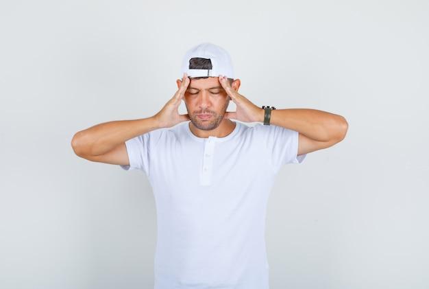 Молодой мужчина в белой футболке, кепке держит голову в руках и выглядит усталым, вид спереди.