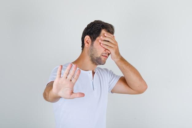 停止ジェスチャーをして目を覆っている白いtシャツの若い男性