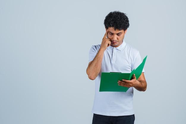 白いtシャツを着た若い男性、クリップボードのメモを見て物思いにふけるパンツ、正面図。