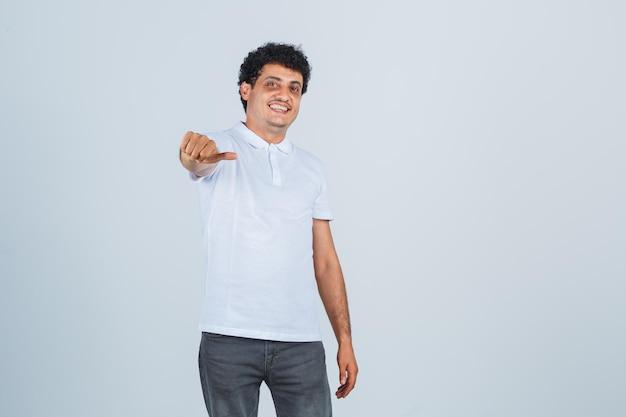 Молодой мужчина в белой футболке, штаны, указывая на камеру большим пальцем и выглядя уверенно, вид спереди.