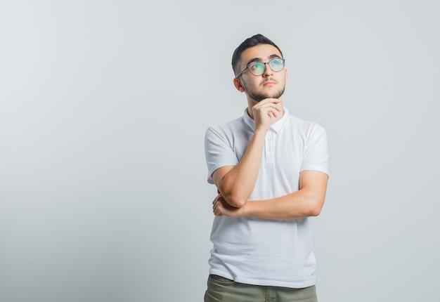 Молодой мужчина в белой футболке, штаны подпирают подбородок рукой и задумчиво выглядят