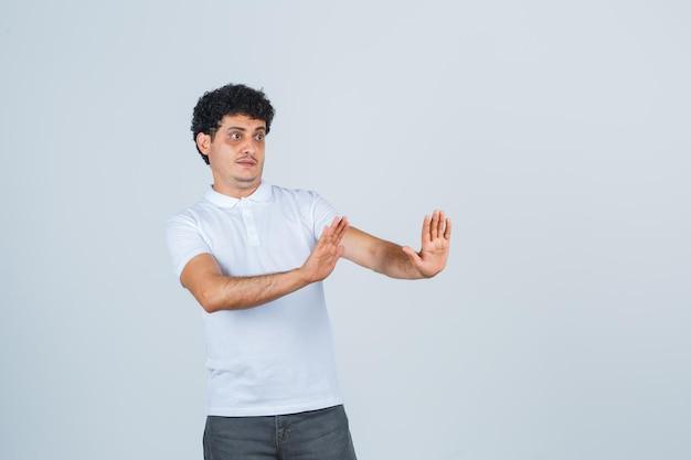 白いtシャツを着た若い男性、停止ジェスチャーを示し、怖がって見えるパンツ、正面図。