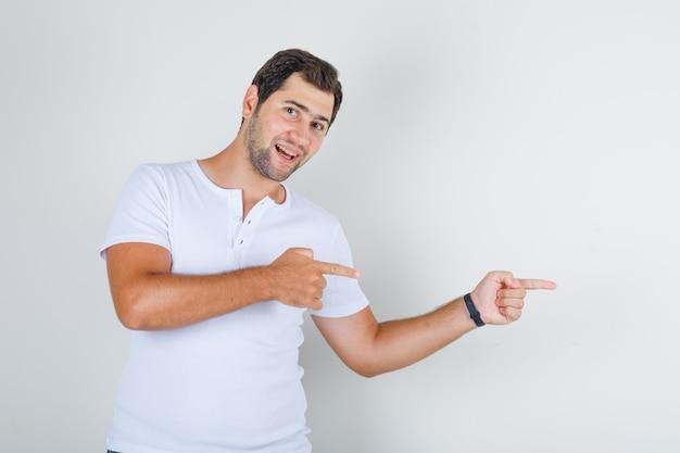 Молодой мужчина в белой футболке показывает пальцем в сторону и выглядит энергичным