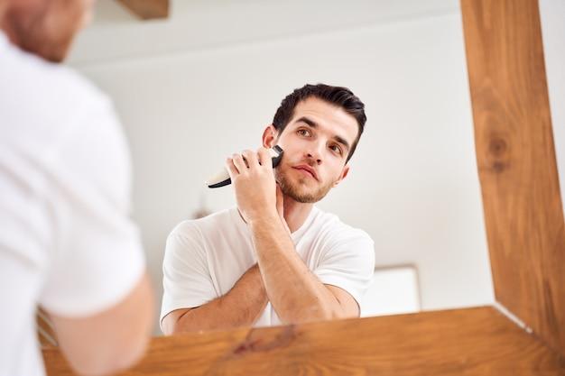 Молодой мужчина в белой футболке бреется, стоя возле зеркала в ванне утром
