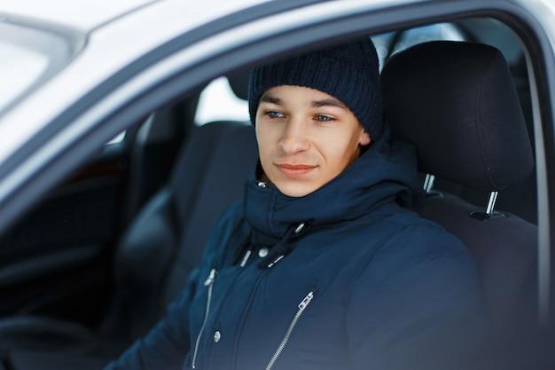 겨울 의류 차에 앉아있는 젊은 남성