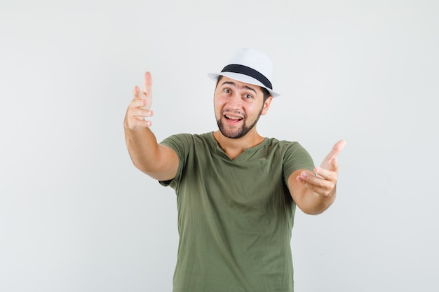 Молодой мужчина приглашает прийти в зеленой футболке и шляпе и выглядит дружелюбно