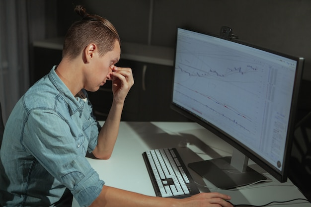 Young male it industry freelancer working late at night