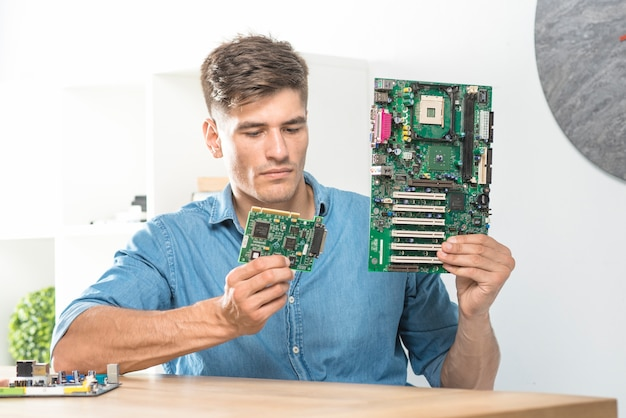 Young male it technician holding two circuits board