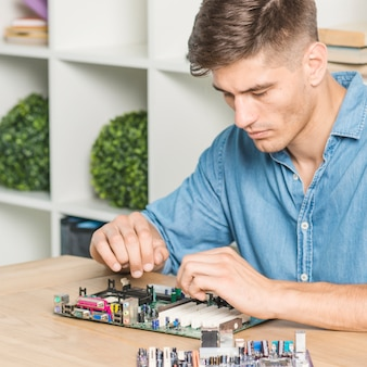 Young male it technician repairing motherboard on table